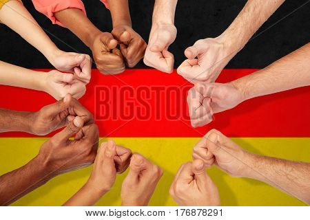 international, diversity, immigration, ethnicity and people concept - hands showing thumbs up over german flag background