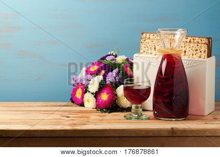 Jewish Passover holiday Pesah celebration concept with matzoh wine and flowers over blue background