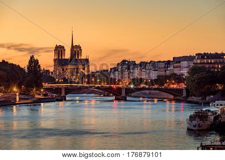 Notre Dame de Paris Cathedral Ile Saint Louis and the Seine River at sunset. Summer evening with the Sully Bridge and city lights in the 4th Arrondissement of Paris. France