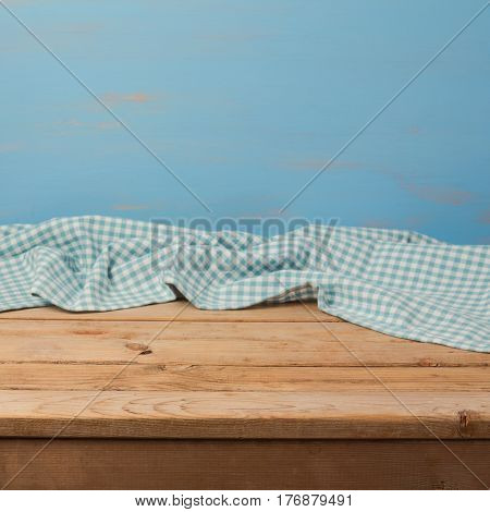 Empty wooden table with checked blue tablecloth over rustic painted wall for product montage display