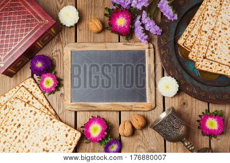 Jewish holiday Passover background with chalkboard matza and seder plate. View from above