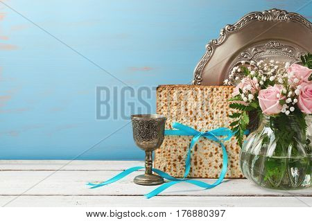 Jewish holiday Passover Pesah background with matzoh rose flowers and wine glass on wooden table with copy space