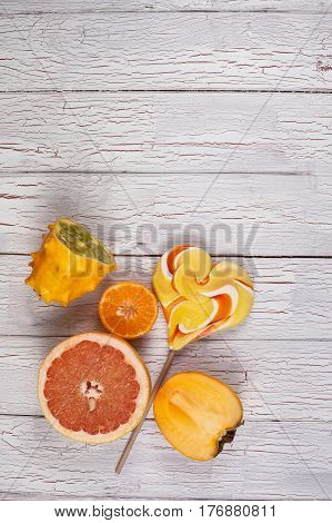 Composition of fresh fruits and sweet lollypop placed on a light wooden board