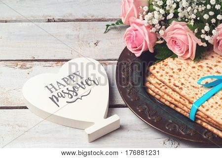 Jewish holiday Passover Pesah concept with matzoh rose flowers and heart shape sign over wooden background