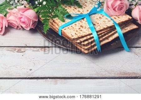 Jewish holiday Passover Pesah background with matzoh and rose flowers