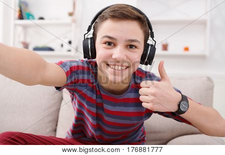 Teenager taking thumb up selfie in headphones on phone while listen to music. Shot of teenage kid gesturing with thumb up while sitting on couch at home