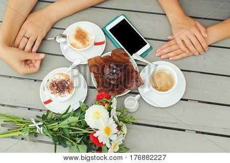 Chocolate muffin with one candle, cups with coffee on the wooden table .