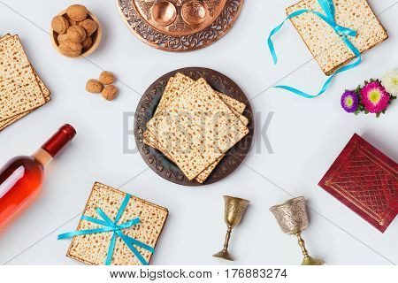 Jewish Passover holiday Pesah celebration concept with matzoh wine and seder plate over white background. View from above. Flat lay