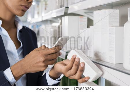 Businesswoman Scanning Barcode Through Smart Phone