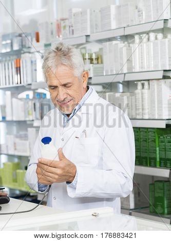 Pharmacist Scanning Barcode Of Shampoo Bottle At Counter
