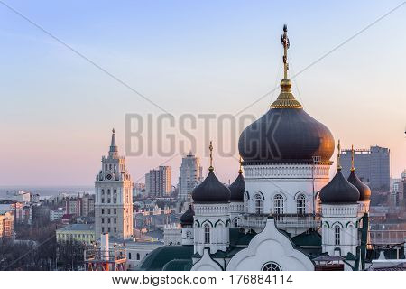 The Annunciation Cathedral (Orthodox Church ) in the center of Voronezh city, Russia, at background of South-East Railway Administration Building sunset