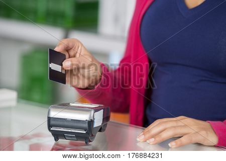 Customer Holding Credit Card Over Reader In Pharmacy