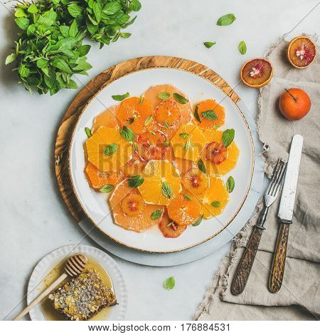 Fresh mixed citrus fruit salad with mint and honey on white ceramic plate over grey background, top view, square crop. Vegan, vegetarian, healthy, dieting, detox food, clean eating concept