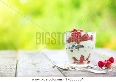 Healthy Layered Dessert With Cream, Muesli And Raspberries On Wooden Table Over Garden Background Wi