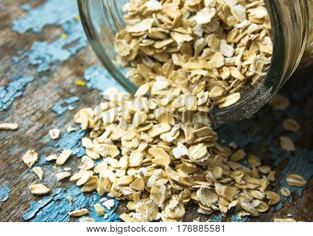 raw oatmeal is scattered on the desk of the bank in which the oat flakes are stored. blue background in the style of Shabby Chic. white spoon with uncooked oatmeal