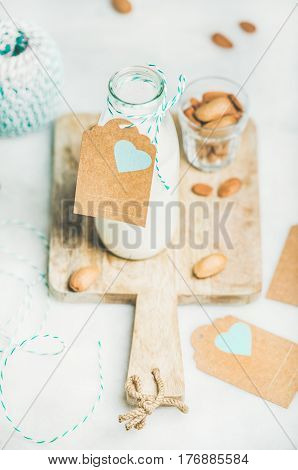 Fresh vegan dairy-free almond milk in glass bottle with craft paper label with copy space on serving wooden board over light grey background. Vegan, vegetarian, raw, clean eating, diet food concept