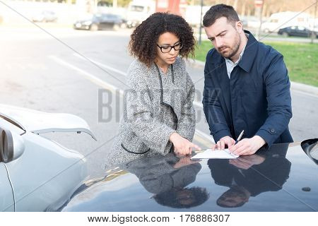 Man and woman filling an insurance car form after bad car crash