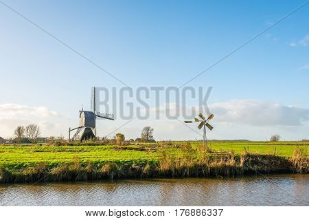 Back of a wooden hollow post mill and a small metal polder mill next to each other in a Dutch polder landscape on a sunny day in autumn.