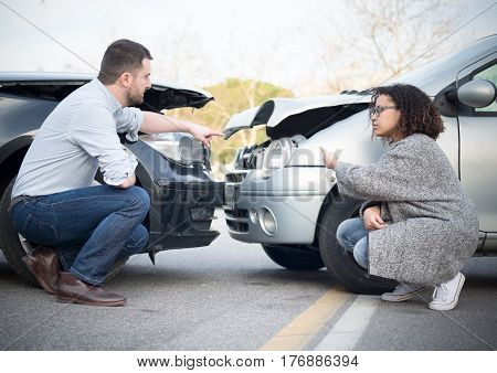 Man and woman arguing after bad car crash