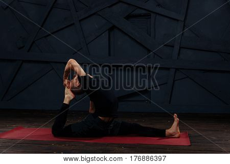 Man practicing advanced yoga against a urban background.