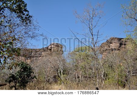 Bhimbetka rock shelters, Madhya Pradesh, India- January 22, 2016: View of Rock Shelters with blue sky and forest area at Bhimbetka archaeological site at Raisen District, Madhya Pradesh, India.