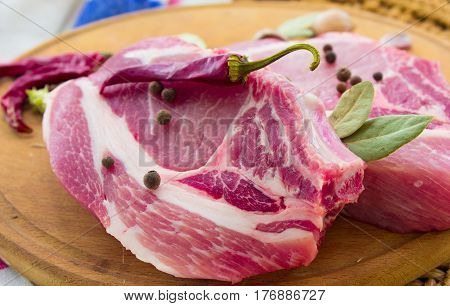 Raw pork steak with spices on a round board With spices and rosemary