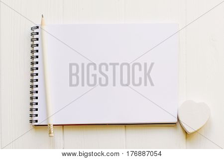 Open notepad with empty page for copy space with a pencil and white wooden heart on wooden milk white background