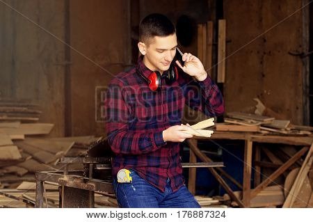 Workman Dressed In The Chekered Shirt Talking The Phone And Looking At The Sawed Wooden Blanks At Th