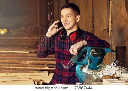 Smiling Workman Dressed In The Checkered Shirt Talking The Phone Near Circular Saw. Timbers On Backg