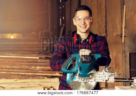 Smiling Workman Dressed In The Checkered Shirt Working With Circular Saw At The Sawmill. Timbers On