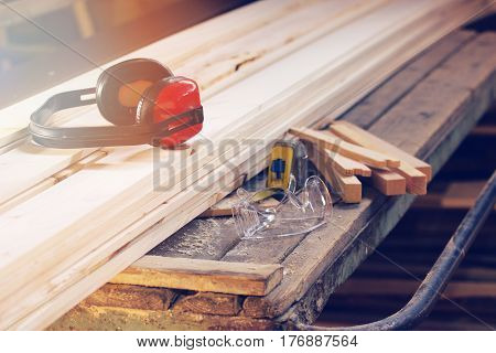 Sawmill factory concept. Protective headphones protective glasses tape-measure and wooden blanks on workplace.
