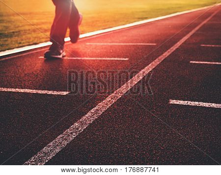 Man Legs In Running Shoes  On Red Racetrack On Outdoor Stadium.