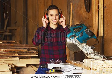Smiling Workman Dressed In The Checkered Shirt And Wearing Protective Headphones Working With Circul