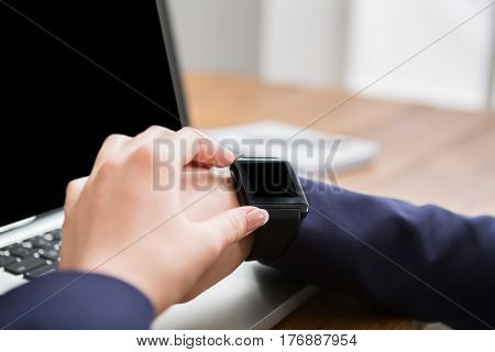 Close-up of woman with smart watch at workplace in office. Girl sitting at wooden table in urban cafe and using digital devices, shallow depth of field