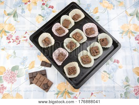 Chocolate brownies on a baking tray with chocolate pieces