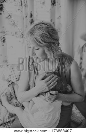 Caring young mother breastfeeds adult baby daughter poster