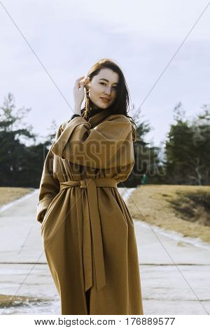 stylish young woman out for a walk. she dressed and looks very fashionable. coat of beige (camel) color and black turtleneck. beautiful woman. she walks in the park.