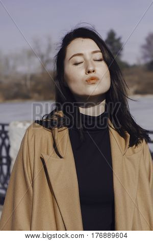 stylish young woman out for a walk. she dressed and looks very fashionable. coat of beige (camel) color and black turtleneck. beautiful woman. she sends a kiss.