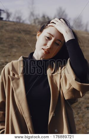 stylish young woman out for a walk. she dressed and looks very fashionable. coat of beige (camel) color and black turtleneck. beautiful woman. girl straightens her hair.