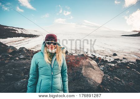 Woman traveler happy smiling with Elbrus mountain on background Travel Lifestyle concept adventure active vacations outdoor mountaineering climbing sport girl wearing down jacket outdoor