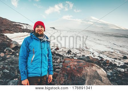 Bearded Man traveler happy smiling with Elbrus mountain on background Travel Lifestyle concept adventure active vacations outdoor mountaineering climbing sport