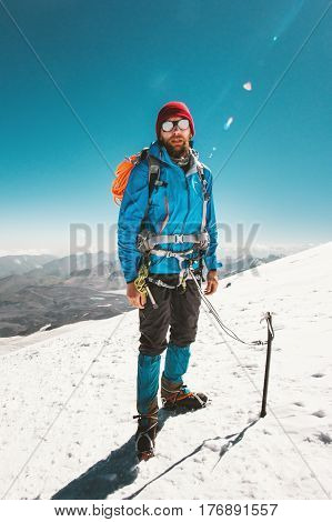 Man alpinist climbing in mountains glacier Travel Lifestyle endurance concept adventure active vacations outdoor mountaineering sport ice axe crampons alpinism equipment