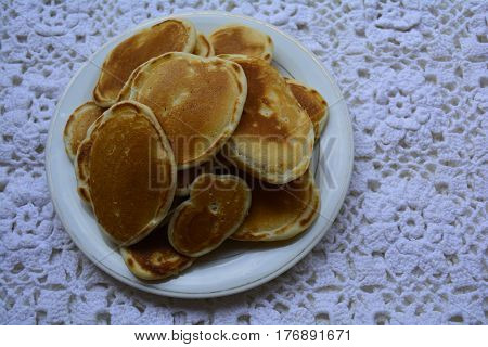 pancakes on white lace tablecloths, plate of pancakes
