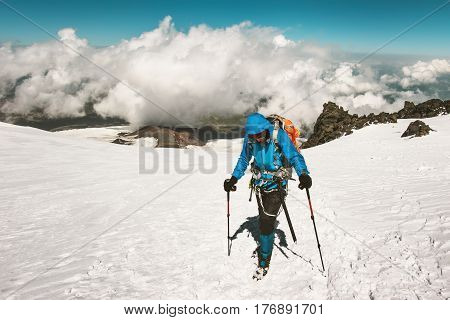 Man alpinist climbing in mountains glacier Travel Lifestyle success concept adventure active vacations outdoor mountaineering sport alpinism equipment clouds on background