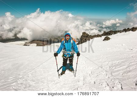 Happy Man alpinist climbing in mountains glacier Travel Lifestyle success concept adventure active vacations outdoor mountaineering sport alpinism equipment clouds on background