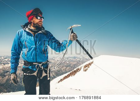 Man climber holding ice axe on mountain glacier Travel Lifestyle concept adventure active vacations extreme outdoor mountaineering sport using alpinism equipment