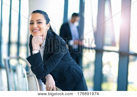 Attractive business woman standing in the hallway of the office building looking at camera