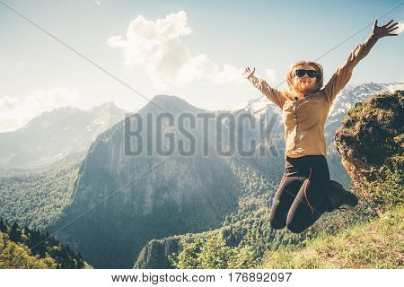 Happy Woman jumping up raised hands mountains on background Lifestyle Travel emotional success wellness concept adventure active summer vacations outdoor
