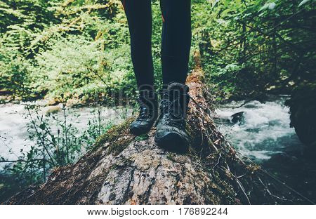 Feet trekking boots Traveler alone crossing over river on woods outdoor in wild forest Lifestyle Travel extreme survival concept summer adventure vacations