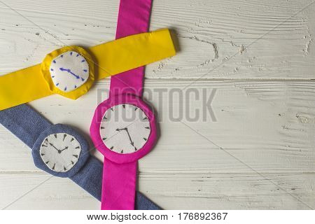 Three Rag Multi Colored Wristwathes on Wooden Background
